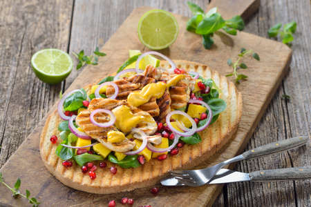 Large toast with grilled chicken on lamb's salad with ripe mango, onion rings, pomegranate seeds and curry sauce Stock Photo