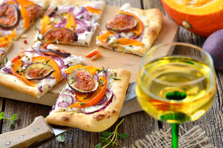 Tarte Flambee from Alsace with goats cream cheese, onions, slices of pumpkins and figs, served with local Alsatian wine Standard-Bild
