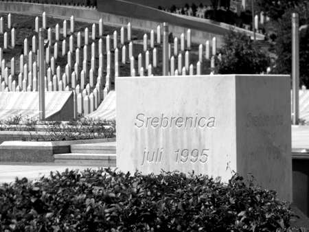 Memorial of Srebrenica massacre in Bosnia Herzegovina with gravestones in the background in black and white colors
