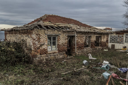 an old house destroyed in time, was once a home. a house on the sea shore not windy, damp and poor weather. abandoned and unsupported house turned into ruins