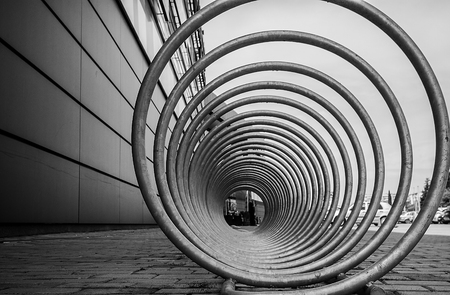 a bicycle stand and a wheelchair space that looks futuristic and interesting. geometric vision and perceptual composition. lines and a tunnel of steel and iron spirals.