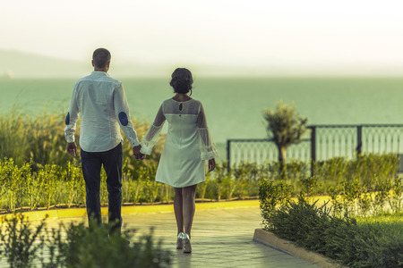 man and woman walking together grasping hands against a beautiful view of sea, ocean and marvelous sky. brides go to the shore of the sea.