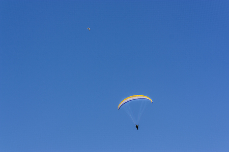 parachutist flies high in the sky with a parachute and has fun and relaxes. flying with a parachute the man enjoys the world from high on a summer blue sky background