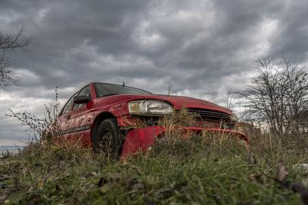 どこか赤い車を忘れてしまった。放置され、壊れた車。美しい灰色の雲と劇的な空の背景に無視されたマシン。 写真素材