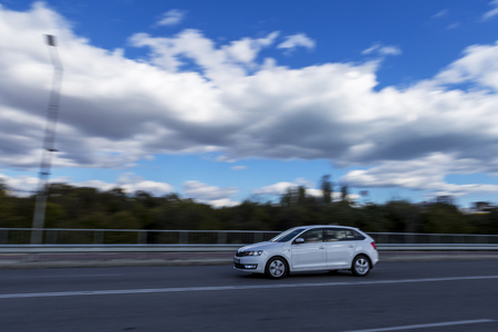 a fast moving car against the backdrop of a beautiful blue sky and fluffy white clouds. Editorial use only. Burgas, Bulgaria. 10.31.2017. light grainy effect for bigger drama and blurry effect.