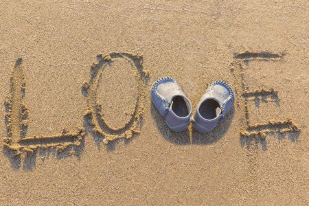 love written in the sand and waiting for a little baby