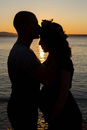 Coppia incinta sulla spiaggia al tramonto. aspettando il bambino. Ragazza incinta in posa con il marito sullo sfondo di un bel tramonto durante l'ora blu.