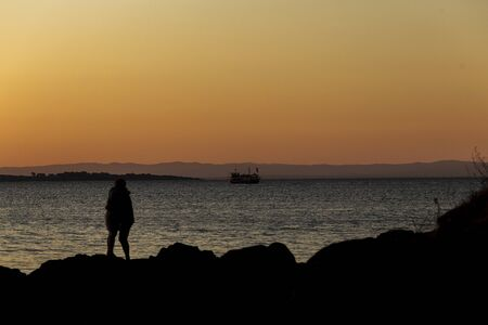 couple in love amidst beautiful sunset and ship on the horizon
