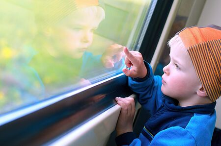 Toddler traveling by train. Little boy is looking out of window and pointing to something which he is interested in. Child concept.