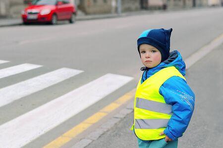 Kind vor Fußgängerüberweg. Ein kleiner Junge findet heraus, ob er den Zebrastreifen überqueren kann. Aus Sicherheitsgründen trägt er eine reflektierende Weste. Auto im Hintergrund. Kind-Konzept. Verkehrskonzept.