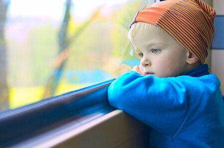 Portrait of boy traveling by train. Portrait of a little sad in a melancholy mood. Child concept.