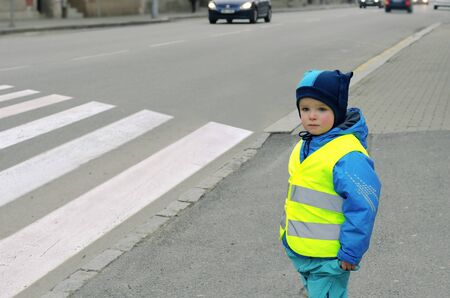 A little boy is going to cross a zebra crossing where a car is approaching. He is wearing yellow reflective vest and jacket with reflective strips because of safety.