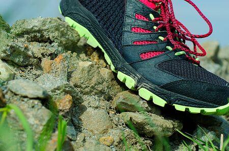 Trailrunning-Schuh auf steinigem Untergrund in Aktion. Laufendes Konzept. Standard-Bild