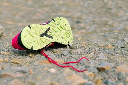 Lost Running Shoe. Running shoe on rough sourface. Running concept.