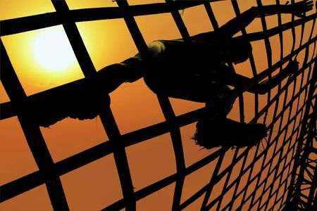 Man climbing a net during sunset. Spartan and gladiator race concept. Banque d'images