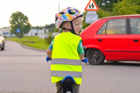 Little boy is going to cross road. . Boy wearing yellow reflective vest and helmet because of safety. There is a red car in the background
