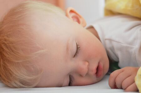 Blond baby boy sweetly sleeping in a bed covered by a blanket.