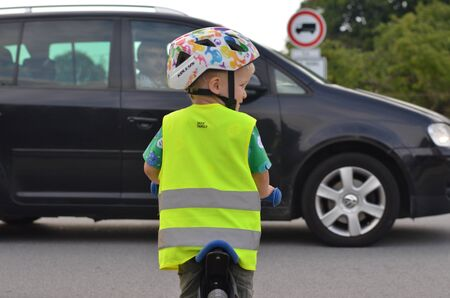Little boy riding a bike and wearing reflective vest and helmet on the road. Driving car in front of him. Standard-Bild