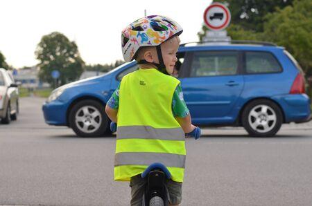 Petit garçon faisant du vélo et portant un gilet réfléchissant et un casque sur la route. Voiture conduite devant lui.