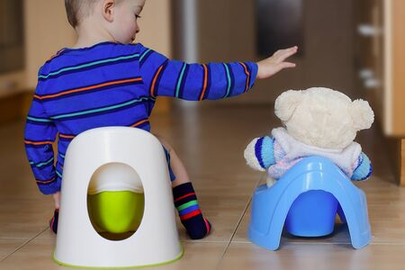 Little boy training in potty with his buddy Imagens