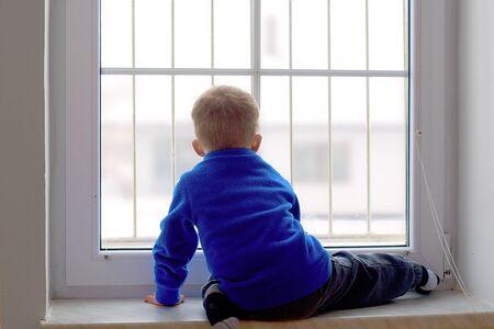 Little boy watching snowy surroundings from window