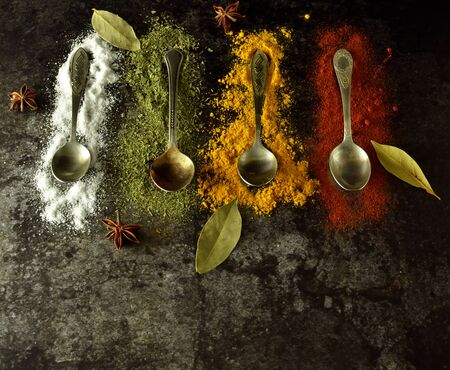 various spices and herbs on spoons on a dark background with free space for writing or recipes