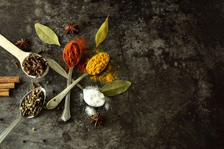 Green herbs, paprika and turmeric on spoons. Cinnamon sticks and spices. Various spices and herbs on spoons on a dark background with copy space for writing or recipes.