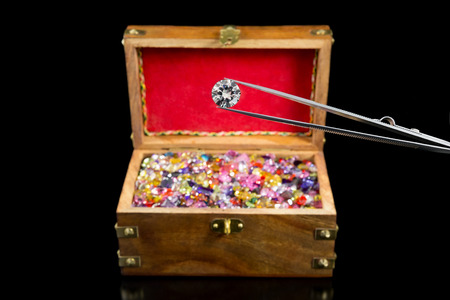 lapidary: A magnificent large white diamond in front of a treasure chest filled with gemstones