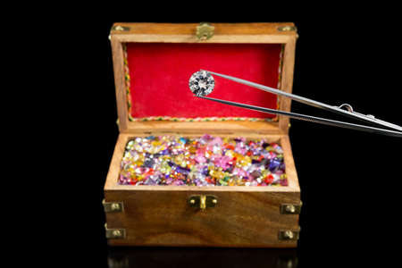 A magnificent large white diamond in front of a treasure chest filled with gemstones