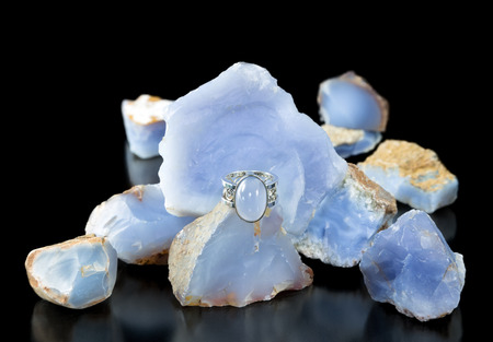 chalcedony: A gold and silver turkish blue chalcedony ring with rough stones in the background Stock Photo