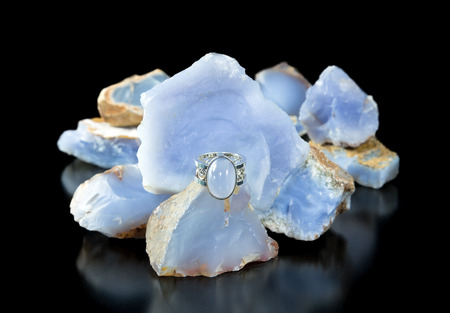 lapidary: A gold and silver turkish blue chalcedony ring with rough stones in the background Stock Photo