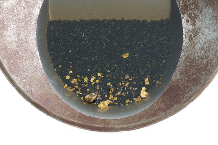 Natural placer gold and nuggets in an old gold pan