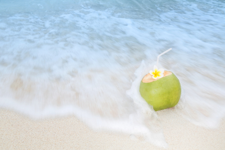 A refreshing tropical drink on a white sand beach with incomming waves Stok Fotoğraf