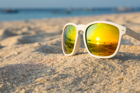 Sunrise on a tropical beach reflected in a pair of sunglasses