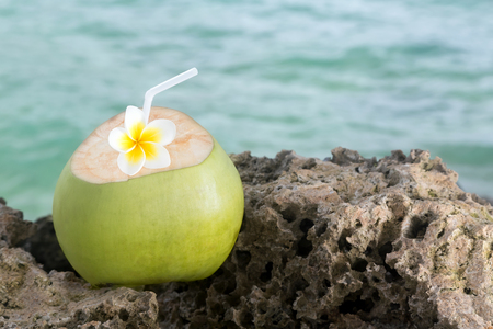 Refreshing tropical drink, with an island paradise in the background
