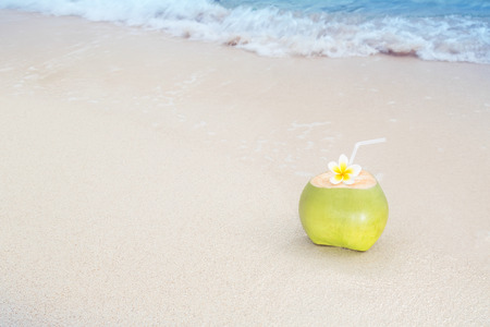 A refreshing tropical drink on a white sandy beach
