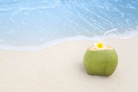 tropical drink: Refreshing tropical drink on a white sand beach with incomming waves Stock Photo