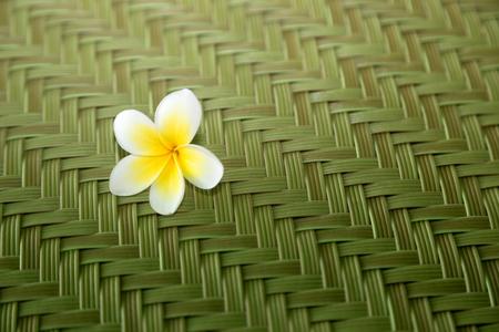 Tropical white plumeria flower on a woven mat