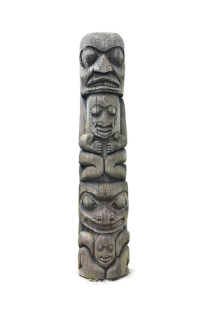 first nations: Traditionally carved West Coast cedar totem pole isolated on a white background Stock Photo
