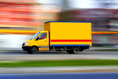 Speedy yellow van always is  on time, panning and blur