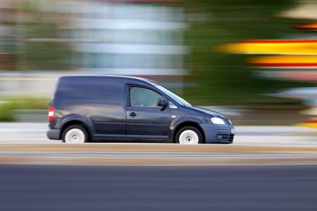 Speedy blauwe minivan is altijd op tijd, panning en vervaging