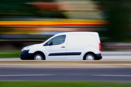Speedy witte minivan gaat op de weg, panning en vervaging Stockfoto