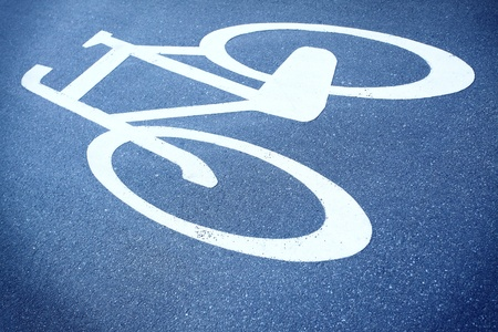 White painted sign for bikes path on blue asphalt photo