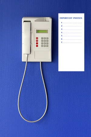 emergency number: Wall phone on blue background, phone concept