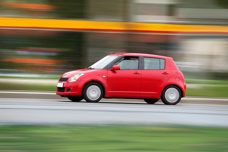Blur small red economical family compact city car photo