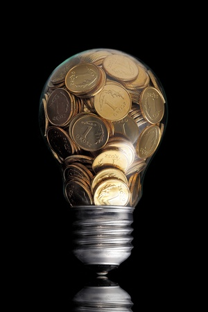 Traditional glass bulb with many golden coins on black photo
