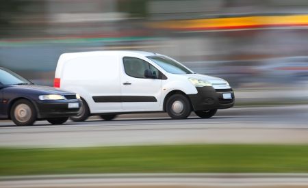 White minivan  on road in traffic jam, panning and blur, transport and business
