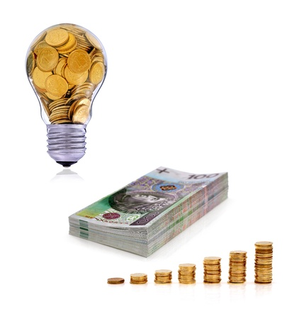 Business symbols and metaphors, golden lightbulb and stack of polish banknote photo