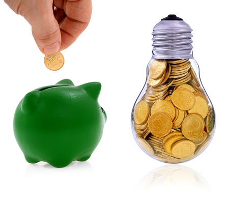 Traditional  lightbulb with  golden coins and green piggy bank, creative business symbols Stock Photo