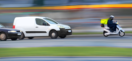 Goods on the phone, speedy blur courier on the way in traffic jam Archivio Fotografico